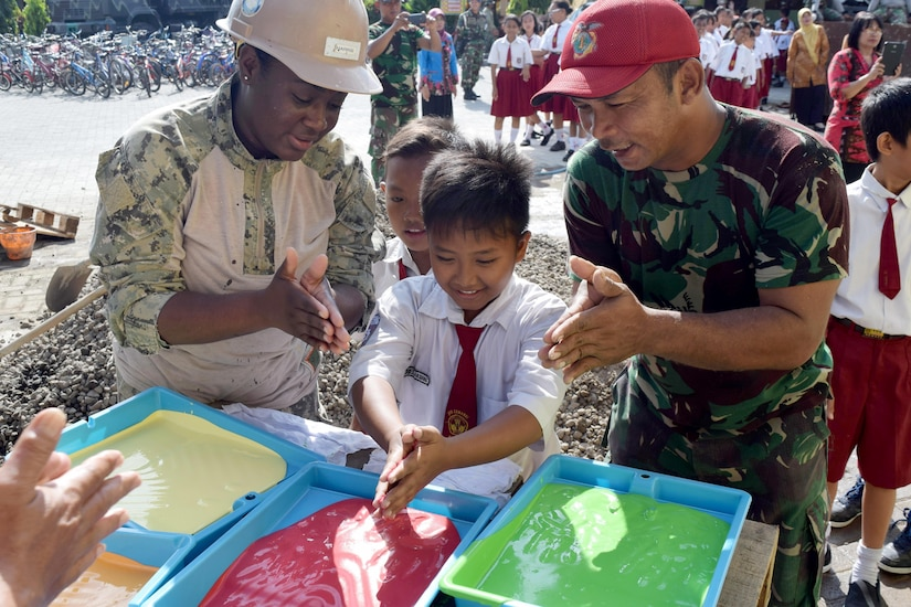 An American sailor and an Indonesian marine play in paint with a child.