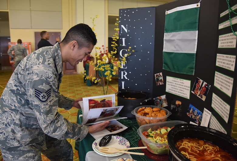 Staff Sgt. Earl Pecson, 81st Diagnostic and Therapeutics Squadron pharmacy technician, views a Nigerian artist book during Diversity Day at the Bay Breeze Event Center Sept. 6, 2017, on Keesler Air Force Base, Miss. The cultural celebration included food sampling and information booths about countries around the world and other special emphasis groups. (U.S. Air Force photo by Kemberly Groue)