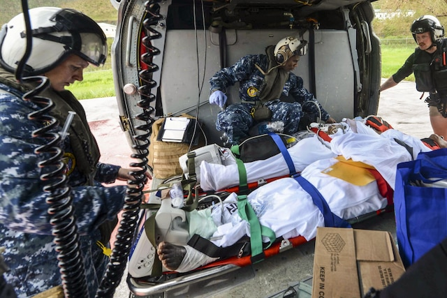 Sailors tend to two patients on stretchers in a helicopter.