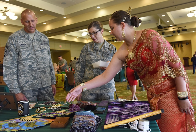 Senior Airman Savannah Slaughter, 81st Comptroller Squadron budget analyst, showcases Thailand memorabilia to Chief Master Sgts. Kenneth Carter, 81st Training Wing command chief, and Julie Bottroff, 81st Medical Group superintendent, during Diversity Day at the Bay Breeze Event Center Sept. 6, 2017, on Keesler Air Force Base, Miss. The cultural celebration included food sampling and information booths about countries around the world and other special emphasis groups. (U.S. Air Force photo by Kemberly Groue)
