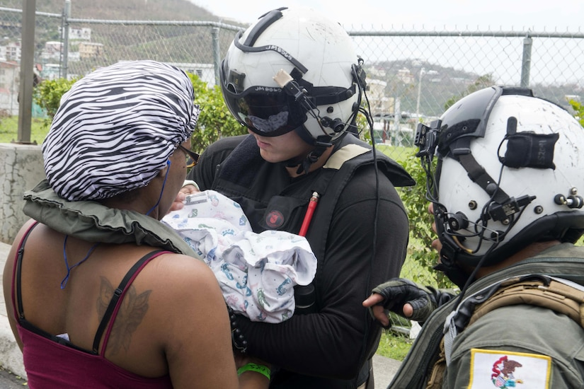 Navy Petty Officer 2nd Class John Malico and Petty Officer 1st Class Erick Sotelo help a mother and child during relief efforts in the U.S. Virgin Islands following Hurricane Irma, Sept. 7, 2017. The sailors are assigned to Helicopter Sea Combat Squadron 22. Navy photo by Petty Officer 2nd Class Nathan Wilkes
