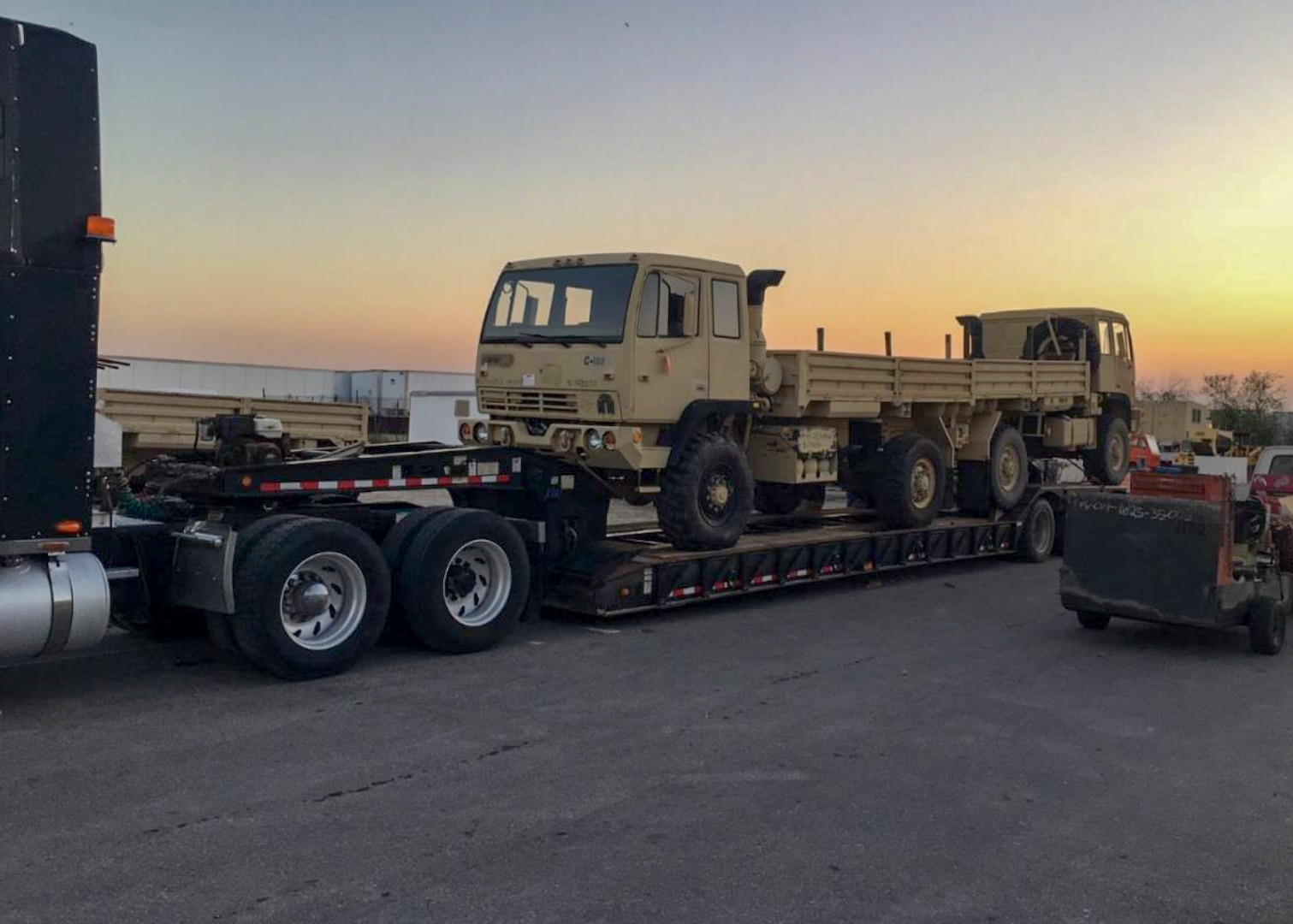Two former military trucks, issued by DLA Disposition Services through the 1033 program to Texas law enforcement, depart the Texas Federal State Property San Antonio Office as the sun sets. The next morning the trucks were operating on the east side of Houston rescuing people from flooding caused by Hurricane Harvey.