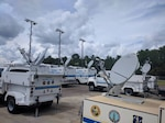 Florida National Guard satellite communications vehicles are gathered at a staging area