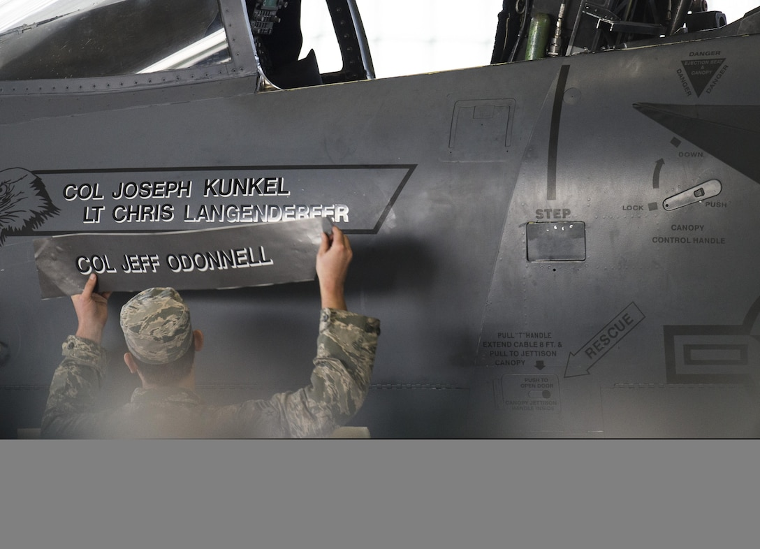 Senior Airman Thomas Ortz, 366th Maintenance Squadron, changes the name on the 366th Fighter Wing flagship F-15E Strike Eagle at Mountain Home Air Force Base, Idaho, Sept. 8, 2017. The change in name is symbolic of Col. Joseph Kunkel's assumption of command of the 366th FW. (U.S. Air Force photo/Senior Airman Samuel Morse)