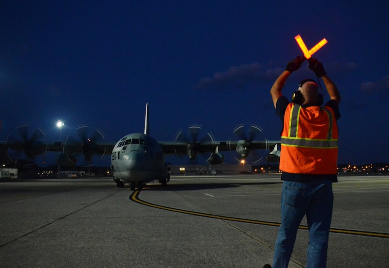 A Dobbins airfield manager guides in a C-130 as it taxis on the flightline at Dobbins Air Reserve Base, Ga. Sept. 6, 2017. The aircraft carried civilian and contract Department of Defense personnel who were evacuated from the Caribbean. (U.S. Air Force photo/Don Peek)