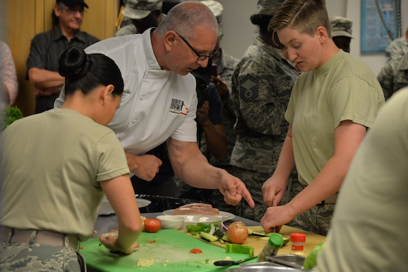 Celebrity Chef Robert Irvine assists Senior Airman Secilia Peraza, left, and Airman First Class Candance Ellenurg, both 90th Force Support Squadron missile field chefs, by coaching them as they prepare their individual dishes during a Warrior Chef Competition Sept. 7, 2017, at Malmstrom Air Force Base, Mont. Chef Irvine was a mentor and a judge for the competition.  (U.S. Air Force phot/Airman First Class Daniel Brosam)