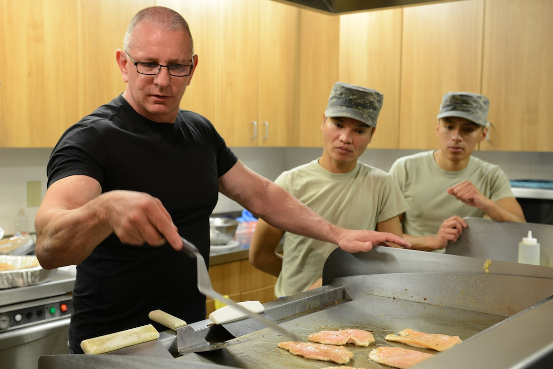 Celebrity Chef Robert Irvine shows Airman First Class Nicki Agunos, center, and Senior Airman Salvador Argumedo, both 341st Force Support Squadron missile field chefs, how to quickly improve the quality and taste of grilled chicken while preparing lunch Sept. 6, 2017, at a missile alert facility near Ulm, Mont. Chef Irvine visited a MAF to better understand the unique challenges missile chefs face and provided feedback on ideas for improving the meal process. (U.S. Air Force photo/Staff Sgt. Delia Martinez)