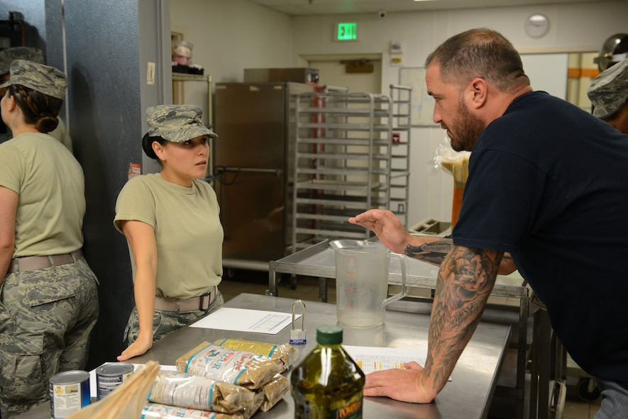 Chef Darryl Moiles explains meal preparation instructions to Senior Airman Secilia Peraza, 90th Force Support Squadron missile field chef, Sept. 6, 2017, at Malmstrom Air Force Base, Mont. Missile field chefs from Malmstrom, Minot AFB, N.D, and F.E. Warren AFB, Wyo., prepared food for the base under the guidance and mentoring from Chefs Robert Irvine and Moiles. (U.S. Air Force photo/Staff Sgt. Delia Martinez)