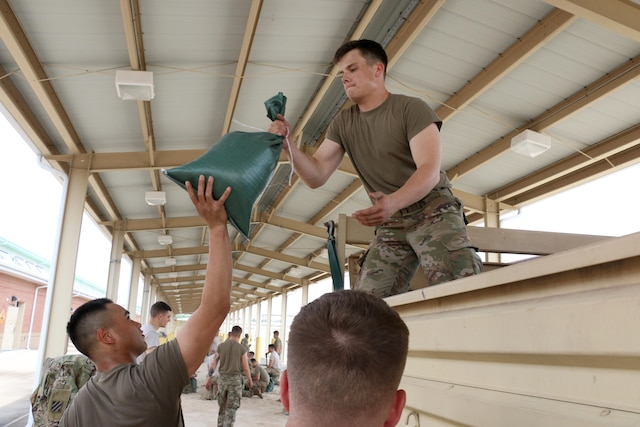 One service member passes a sandbag to another.