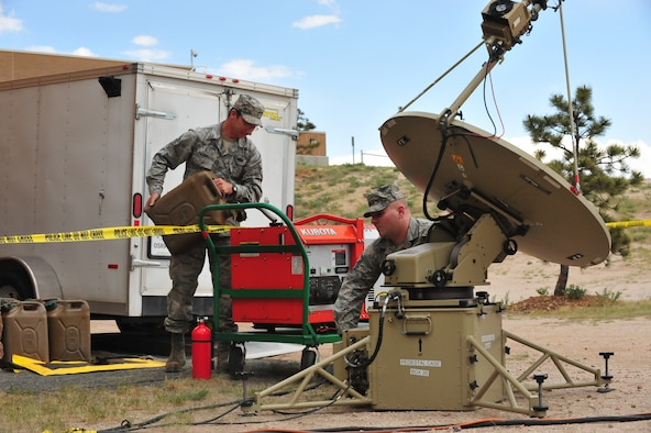 Two Airmen operate communications equipment