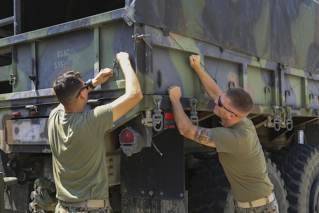 Two Marines secure a tarp onto a truck.