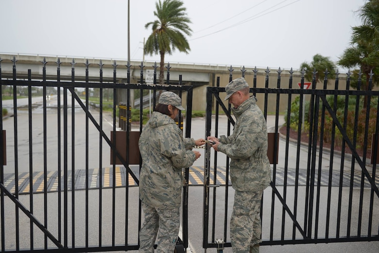 CMSgt Kimberly Vinson, 45th Space Wing command chief, and Brig. Gen. Wayne Monteith, 45th Space Wing commander, lock the Patrick Air Force Base, Florida, gates in preparation for Hurricane Irma, Sept. 10, 2017. HURCON I indicates surface winds in excess of 58 mph could arrive within 12 hours.