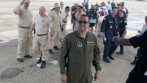 U.S. Air Force Tech Sgt. George Parkhurst, 156th Operations Group flight, and local first responders await the arrival of the 156AW WC-130H Hercules aircraft transporting U.S. ciitizens rescued from the Caribbean island of St. Maarten, Sept.9.