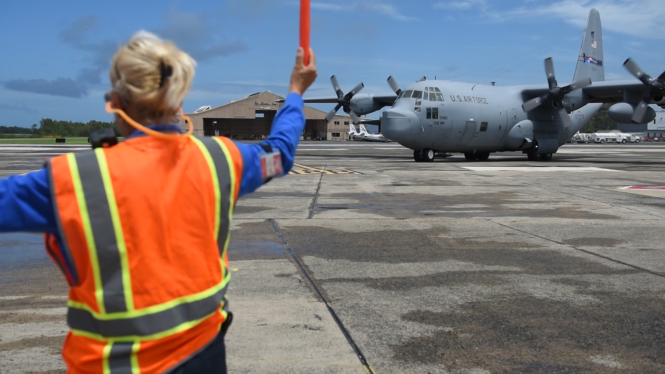 A 156th Airlift Wing - Puerto Rico Air National Guard WC-130H Hercules aircraft is marshaled into a parking spot on the Luis Muñoz Marin International Airport in Carolina, Puerto Rico.