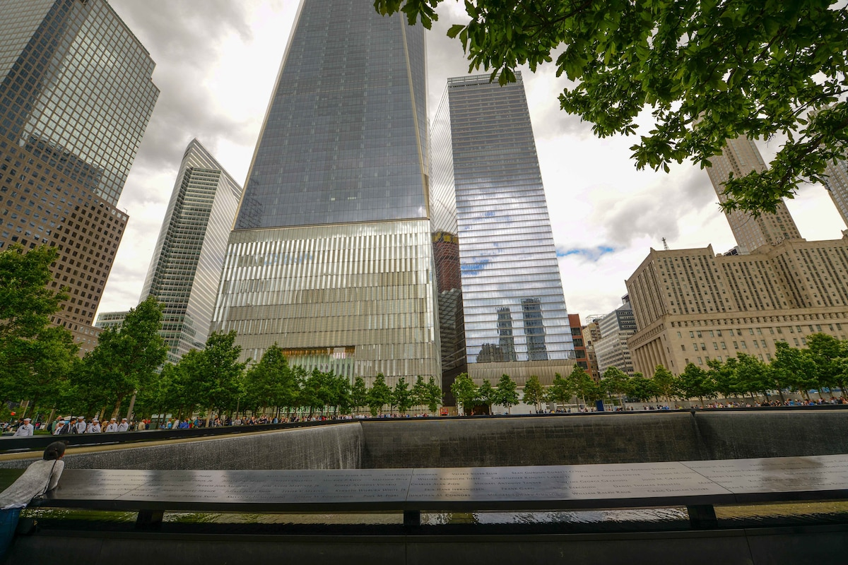 Service members and visitors are seen at the 9/11 memorial plaza.