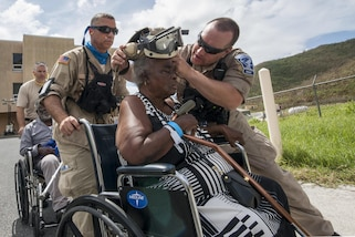 A man helps a woman in a wheelchair put on protective eye wear.