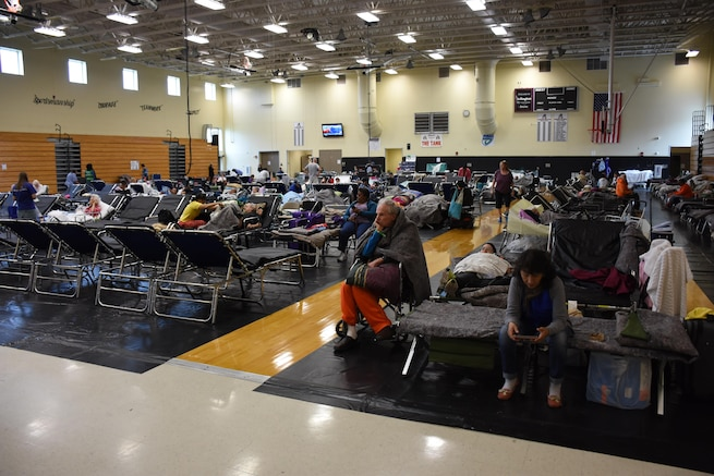 Floridians settle in at a shelter for residents with special needs set up at a high school in Jacksonville, Fla., Sept. 9, 2017. Florida Air National Guardsmen assigned to the 125th Fighter Wing assisted citizens at the shelter. Air National Guard photo by Master Sgt. William Buchanan