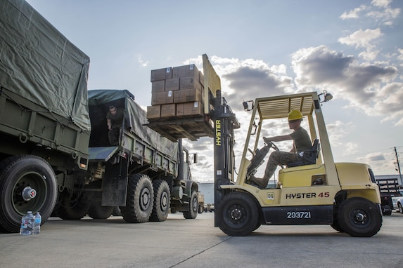 A Marine uses a forklift to lift cardboard boxes near a waiting truck.