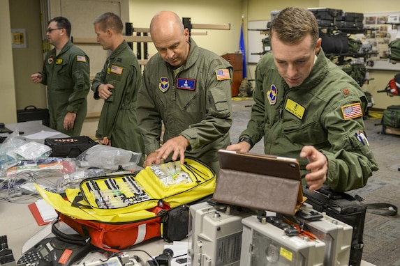 Airmen handle medical supplies on a table.