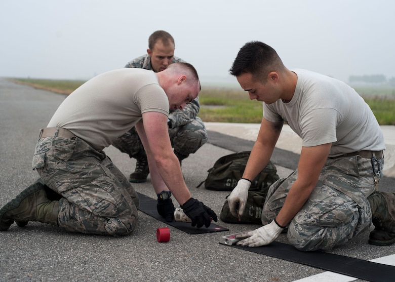U.S. Air Force Airmen assigned to the 8th Civil Engineer Squadron replace the old end of the nylon tape used for the aircraft arresting system at Kunsan Air Base, Republic of Korea, Sept. 9, 2017. The system includes a 1.25-inch steel cable attached to 1,200 feet of the nylon tape wrapped in a large metal reel.  When activated, the reel spins and activates a hydraulic pump which compresses brake pads. Safely bringing the aircraft to a halt in a controlled fashion. (U.S. Air Force photo by Staff Sgt. Victoria H. Taylor)