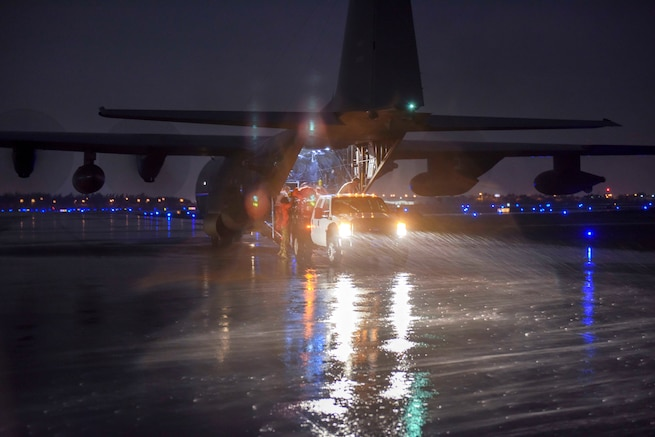 Coast Guard and Air Force personnel offload supplies and gear from an airplane at night.