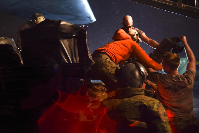 Coast Guard and Air Force personnel offload supplies and gear from an aircraft at night.