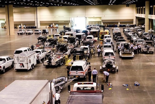 Groups of people and emergency vehicle congregate in an indoor facility.