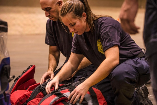 Two people kneel over red bags prepping equipment.
