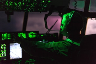A member of the Air Force sits at the controls of an airplane with clouds visible though the windscreen.