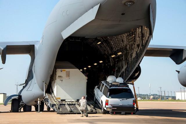 Airmen upload equipment and supplies onto an aircraft.
