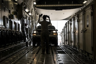 A member of the Air Force makes hand signals as a vehicle drives into an aircraft.