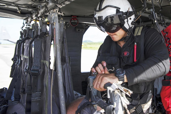 A sailor preps a helicopter to transport cargo.