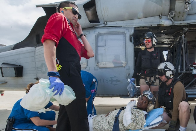 Sailors put a patient on a helicopter.