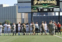 Soldiers assigned to the 354th MPAD, Coraopolis, Pennsylvania, fist bump members of the Point Park University's men's soccer team during a military appreciation game in Pittsburgh September 9, 2017. The 354th MPAD planned a training scenario that allowed the soldiers to practice photography and videography during the game