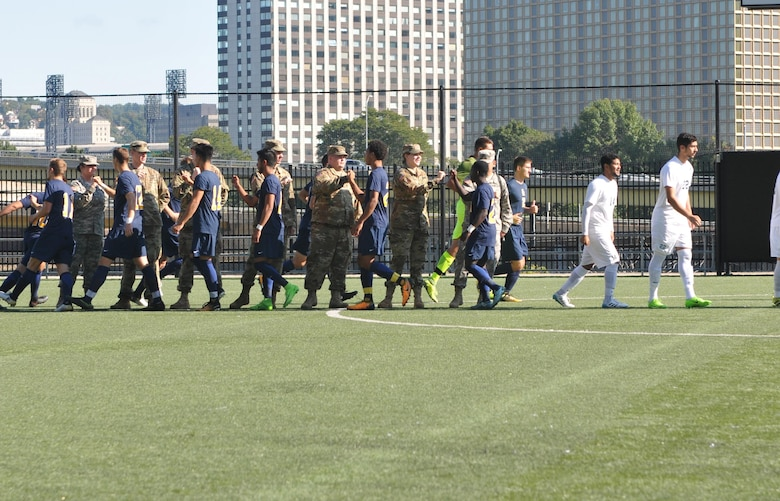 Soldiers assigned to the 354th MPAD, Coraopolis, Pennsylvania, fist bump members of the Point Park University's men's soccer team during a military appreciation game in Pittsburgh September 9, 2017. The 354th MPAD planned a training scenario that allowed the soldiers to practice photography and videography during the game.