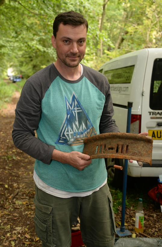 Volunteer shows stove grate recovered during archeological dig