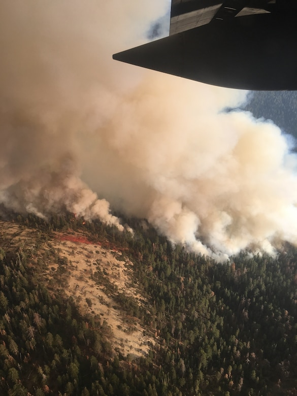 Smoke and the start of a fire retardant containment line dropped by a Modular Airborne Fire Fighting System-equipped C-130 Hercules aircraft near California's South Fork Fire, south of Yosemite National Park are visible, Aug. 14, 2017.