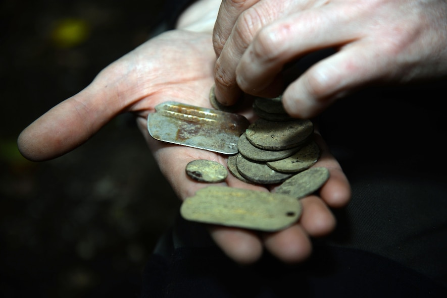 A volunteer hold dog tags and coins recovered from archeological dig