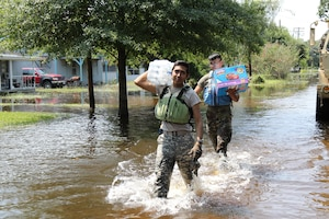 Pfc. Bryan Quiroz and Pvt. Andres Lopez from 3-133rd Field Artillery carry clean water and pull-ups to Orange residents.
