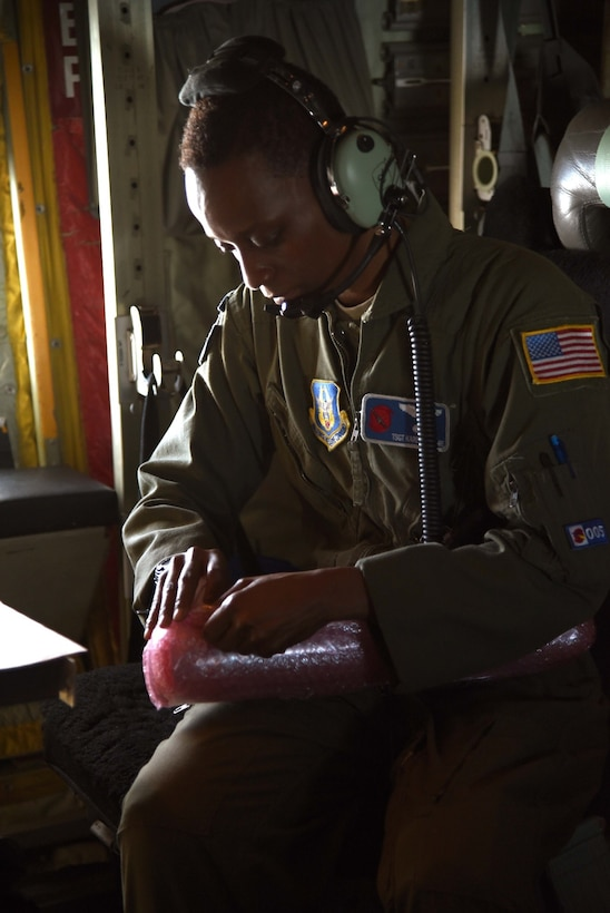 Tech. Sgt. Karen Moore, a loadmaster for the 53rd Weather Reconnaissance Squadron, prepares a dropsonde to be released into the eyewall of Hurricane Irma. Crews have recently been flying missions continuously in three different hurricanes in the Atlantic region simultaneously.