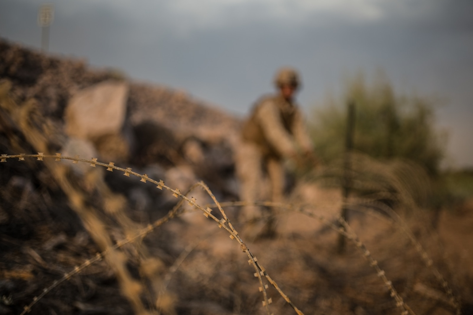 A U.S. Marine with Bridge Company, 7th Engineer Support Battalion, 1st Marine Logistics Group, lays down concertina wire during Exercise Deep Strike II at Blythe, Calif., Sept.6, 2017. Concertina wire is strategically placed and used to simulate setting up a forward operating base (FOB) while deployed. The concertina wire and other defensive barriers are used keep unknown persons out of the FOB and to control access. (U.S. Marine Corps photo by Lance Cpl. Timothy Shoemaker)