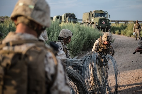 U.S. Marines with Bridge Company, 7th Engineer Support Battalion, 1st Marine Logistics Group, prepare to move concertina wire to various locations during Exercise Deep Strike II at Blythe, Calif., Sept. 6, 2017. Concertina wire is strategically placed and used to simulate setting up a forward operating base (FOB) while deployed. The concertina wire and other defensive barriers are used keep unknown persons out of the FOB and to control access. (U.S. Marine Corps photo by Lance Cpl. Timothy Shoemaker)