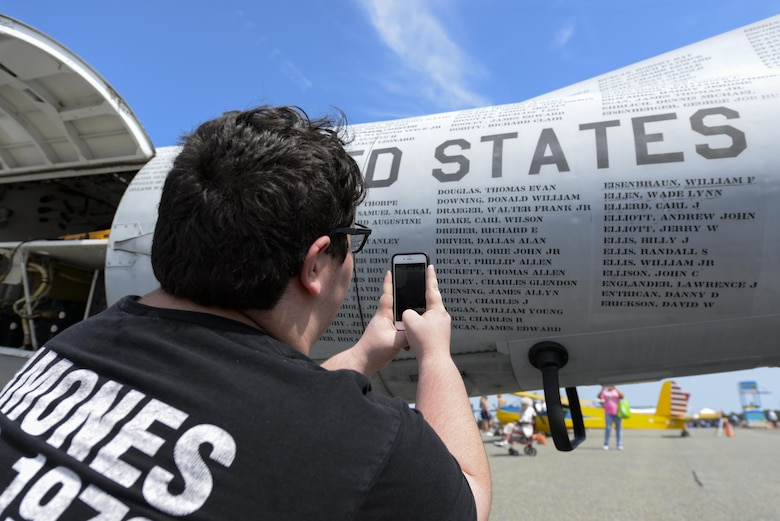 A guest of Team Dover takes photos of names on Mohawk Airshow's Army OV-1 Mohawk Vietnam POW/MIA flying monument. The Army flew the OV-1 during the Vietnam War through Operation Desert Storm to gather battlefield surveillance and provide light strike capabilities. (U.S. Air Force photo by Staff Sgt. Aaron J. Jenne)
