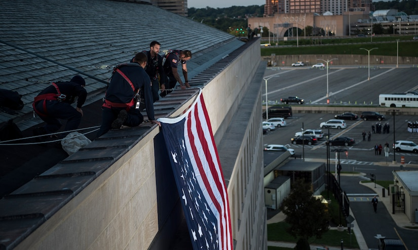 Pentagon workers unfurl a large American flag over the west side of the Pentagon at sunrise, Sept. 11, 2017, on the 16th anniversary of the 9/11 terrorist attacks. During the attacks, 184 people were killed when American Airlines Flight 77 crashed into the western side of the Pentagon near Corridor 4. DoD photo by Air Force Tech. Sgt. Brigitte N. Brantley