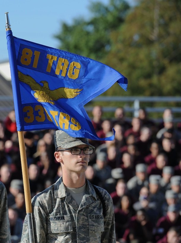 """Airman 1st Class Seth Wachman, 336th Training Squadron freestyle drill team member, carries his squadron's guidon during the 81st Training Group drill down on the Levitow Training Support Facility drill pad Sept. 8, 2017, on Keesler Air Force Base, Mississippi. Airmen from the 81st TRG competed in a quarterly open ranks inspection, regulation drill routine and freestyle drill routine. The 334th TRS """"Gators"""" took first place this quarter. (U.S. Air Force photo by Kemberly Groue)"""
