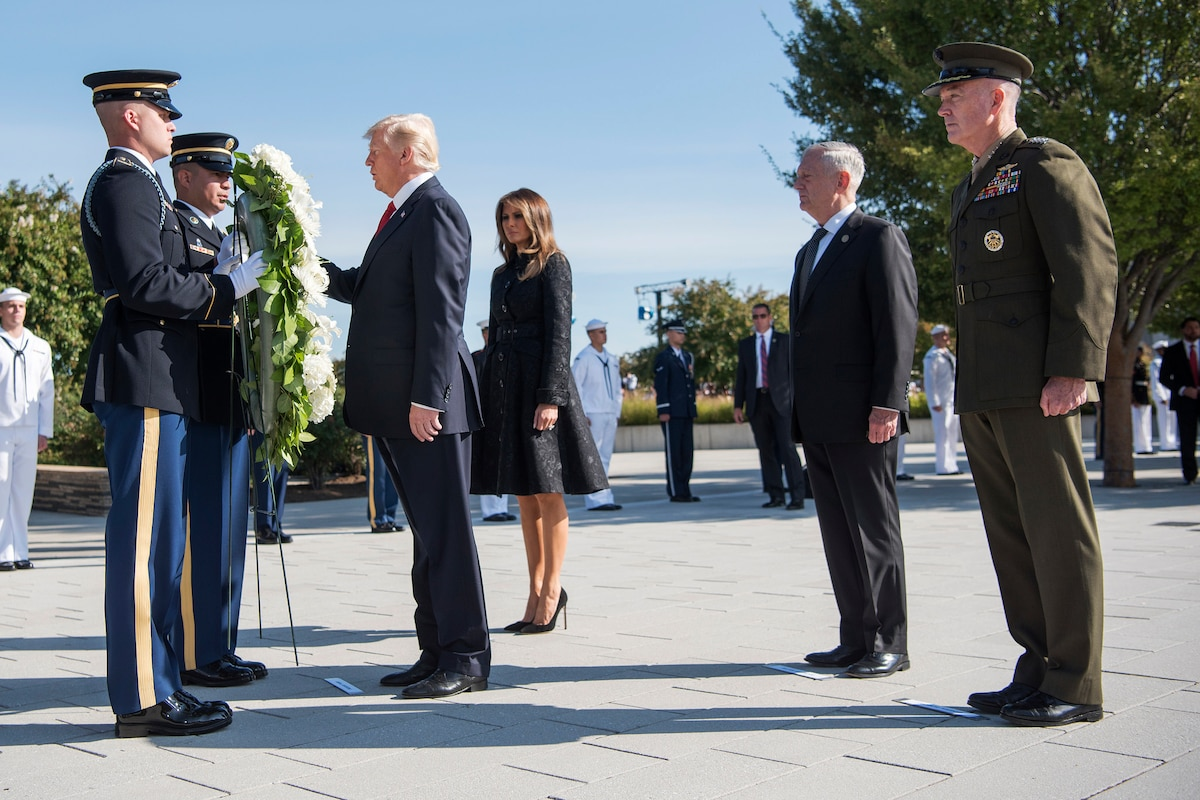President Donald J. Trump touches a wreath with his wife beside him and Defense Secretary Jim Mattis and Marine Corps Gen. Joe Dunford behind them.