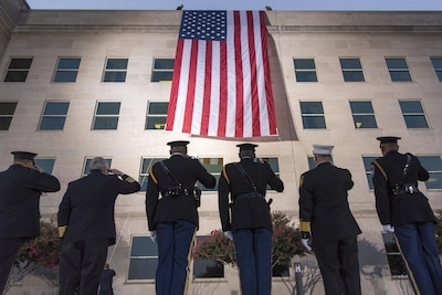 Service members look up to salute an American flag that hands off the roof of the Pentagon.