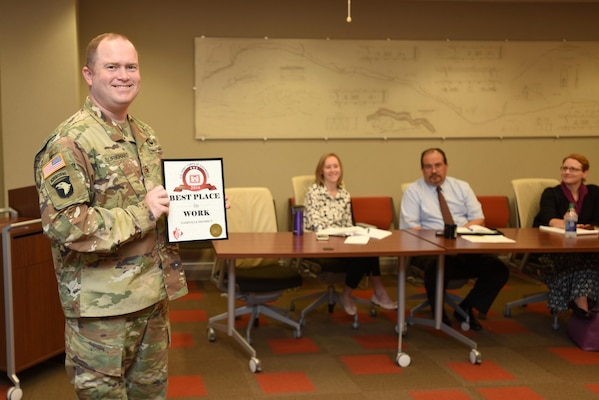"Maj. Christopher Burkhart, U.S. Army Corps of Engineers Nashville District deputy commander, shows off the ""Best Place to Work in USACE"" Award at the district's staff meeting Sept. 11, 2017 in Nashville, Tenn.  The award was in the medium size agency category based on employee responses in the 2016 Federal Employee Viewpoint Survey.  Nine awards were presented by the U.S. Army Corps of Engineers Headquarters to organizations in this category."