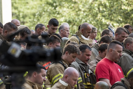 Participants of the 2017 Richmond 9/11 Memorial Stair Climb bow their heads in prayer