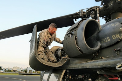 A solider kneels inspecting a helicopter.